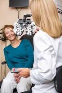 Happy senior woman undergoing eye checkup while optometrist adjusting phoropter in store