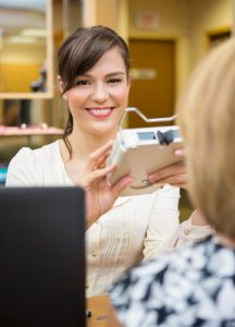 Young female optometrist measuring pupilary distance on senior customer